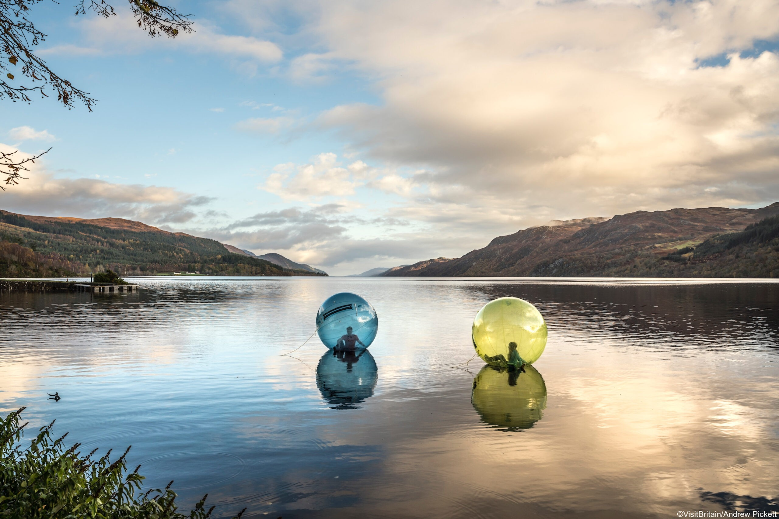 Two people zorbing, sitting in large plastic clear globes floating on the surface of Loch Ness, Highlands, Scotland. TIF file available upon request - please contact info@visitbritainimages.com